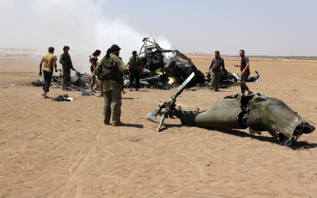 A photo taken on 1 August, 2016 reportedly shows Syrian rebels gathered round the wreckage of a downed Russian military helicopter.