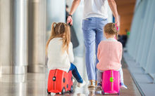 Children at airport with suitcases