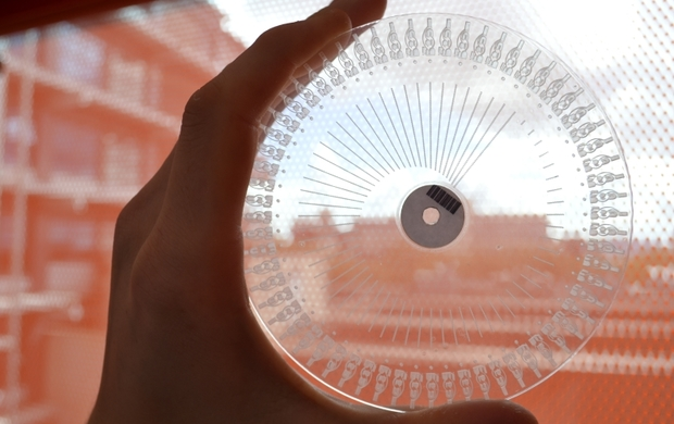 An example of a transparent disc, with carved channels and wells visible, used to analyse milk samples.