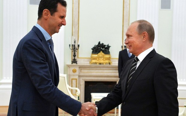Vladimir Putin (R) shakes hands with his Bashar al-Assad during a meeting at the Kremlin in Moscow in October 2015.