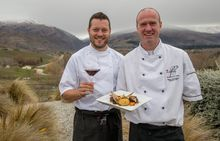 Mark Southon and Werner Hecht-Wendt with dish and wine in front of Mount Difficulty