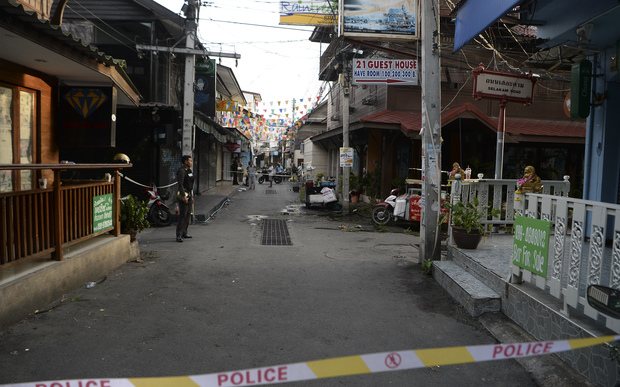 A police officer, left, stands guard where a small bomb exploded in Hua Hin on 12 August.