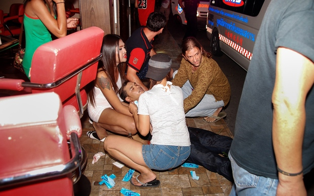 An injured man receives help after a string of bombings in the Thai resort of Hua Hin, near Thailand.