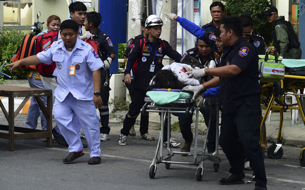 Rescue workers help an injured victim after a string of small bombs exploded in the Thai resort town of Hua Hin.