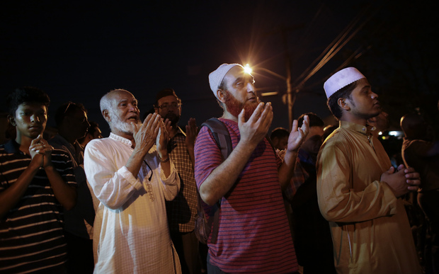 Community members pray outside the Al-Furqan Jame Mosque in Ozone Park after the fatal shootings.