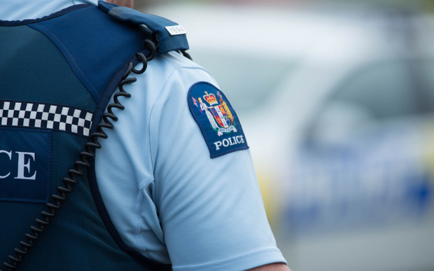 Close up of a police officer at an incident on a residential street. 6 July 2016.