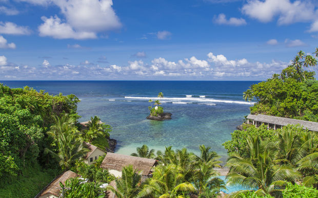Tropical Samoan resort with clear blue waters, white sand and coconut palms