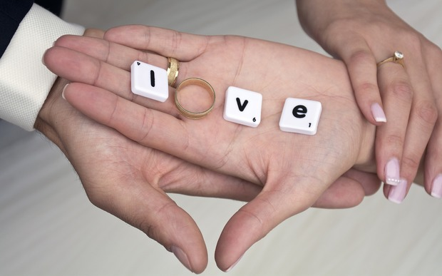 A hand with scrabble letters and an engagement ring spelling love.