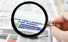 Magnifying glass on job ads.