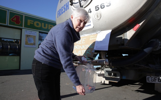 Gail O'Donnell collects drinking water from a tanker.