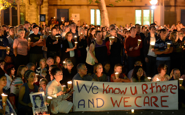 People attend a candlelight vigil in support of asylum seekers, in Sydney on February 23, 2014.
