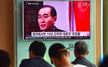People watching a news broadcast showing file footage of Thae Yong-ho at a railway station in Seoul.