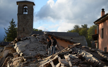 Two men walk on a damaged home after a strong heartquake hit Amatrice
