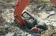 A borrowed digger got stuck in the wetland while digging the illegal pond.