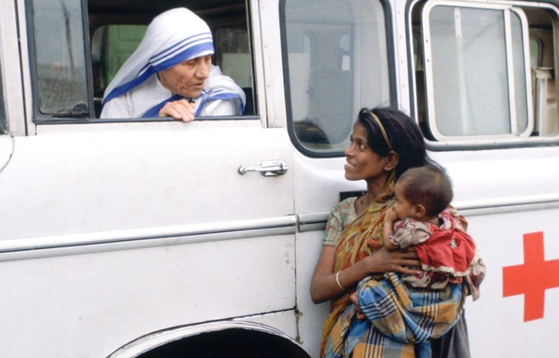 Mother Teresa talking with a poor woman and her child from a Red Cross minibus in Calcutta, India.