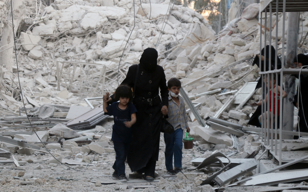 A Syrian family following a reported airstrike on the  al-Muasalat area in the northern Syrian city of Aleppo.
