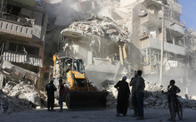 A tractor clears rubble away in Aleppo as relentless airstrikes on the city continue.