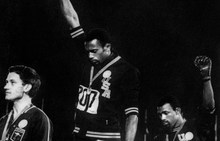 US athletes Tommie Smith, centre, and John Carlos, right, raise their gloved fists in the Black Power salute to express their opposition to racism in the US.