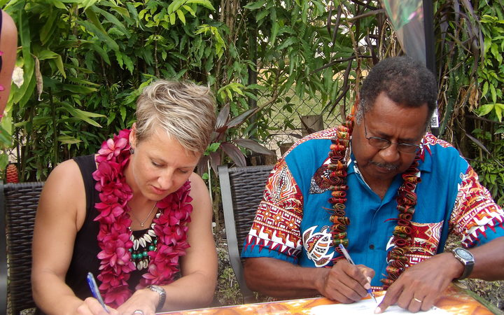 Nicky Barnes signing contract in Vanuatu