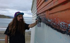 Street artist DSIDE goes to work on the Lyall Bay Surf and Life Saving Club.