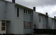Row of two storey weatherboard houses with boarded up windows