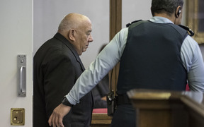 Sir Ngatata Love is escorted by a guard during his trial in the High Court in Wellington on 6 October 2016.