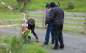 People place flowers at the entrance to the Kinohaku property where three bodies were found, including that of Ross Bremner.