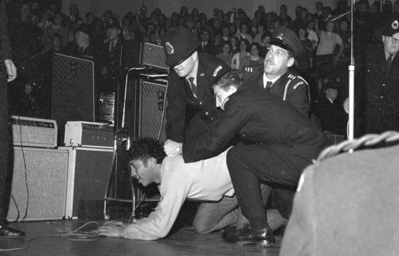 The second Beatles' concert at the Wellington Town Hall on 23 June 1964. Two policemen and a security guard are restraining a fan near the stage. from The Dominion Post Collection, Alexander Turnbull Library