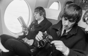 Beatles Ringo Starr and George Harrison on a plane with book and camera.