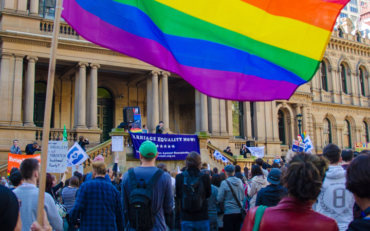 A protester waves a rainbow coloured flag at a marriage equality rally outside Town Hall in Sydney, Australia on August 9, 2015.