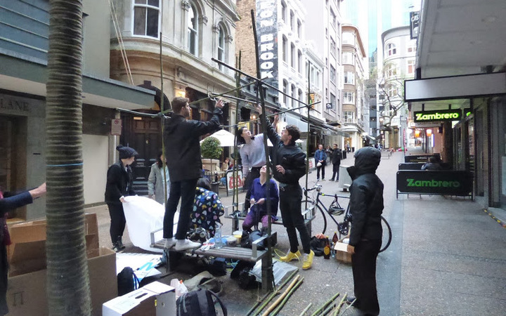 People assemble the Vulcan Lane sculpture (for the first time) before police asked council workers to remove it.