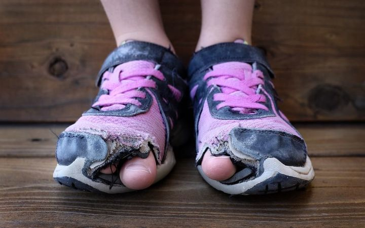 A child's feet in torn, old shoes.