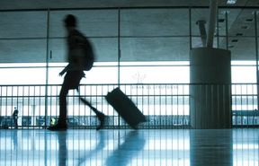 Person at airport with luggage, silhouette.