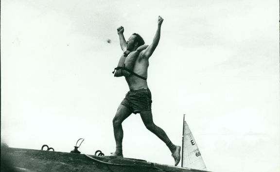 n image of Stephen Sherie on the hull of the USS Haddo, arms raised aloft.