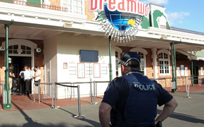 A police officer stands in front of the Dreamworld theme park on Gold Coast after the deaths of four people on a rapids ride.