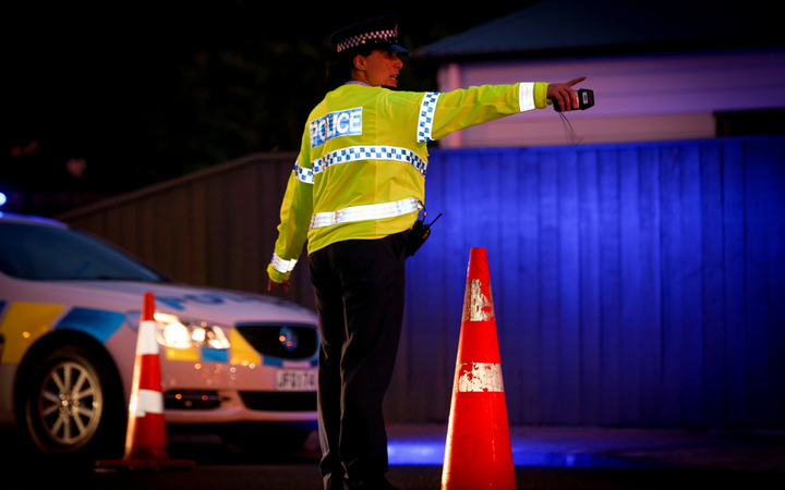 A police officer directing traffic at an alcohol check point.