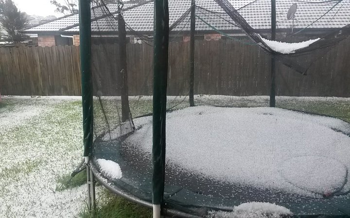 Hail fills a trampoline in a west Auckland backyard.