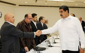 Venezuela's President Nicolas Maduro (R) shaking hands with Venezuelan opposition spokesman Jesus Torrealba, before a meeting between Venezuela's government and opposition leaders in a bid to settle the country's deepening political crisis
