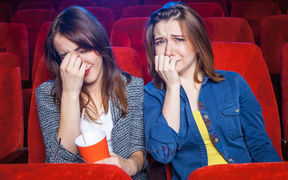 Women cry in a movie cinema.