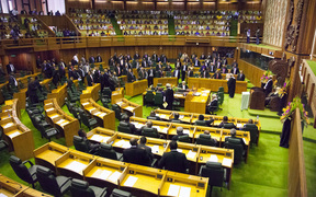Members of parliament stand to the right of the speaker (R) to approve the vote of Peter O'Neill as prime minister in Port Moresby on August 3, 2012.