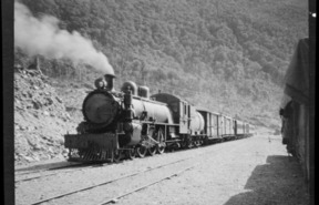 Goods and passenger steam train at unidentified railway station on the West Coast, circa 1910s-1930s