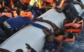 Migrants panic as they fall in the water during a rescue operation by the Topaz Responder ship, run by NGOs.