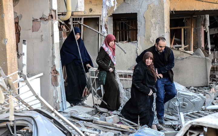 A man and women leave a damaged building at the site of an explosion on 4 November 2016 after a strong blast in Diyarbakir.