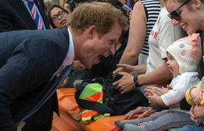 Prince Harry making a silly face at a baby