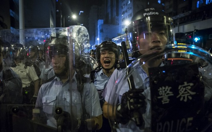 A police officer yells instructions during a protest against an expected interpretation of the city's constitution, the Basic Law, by China's NPCSC.