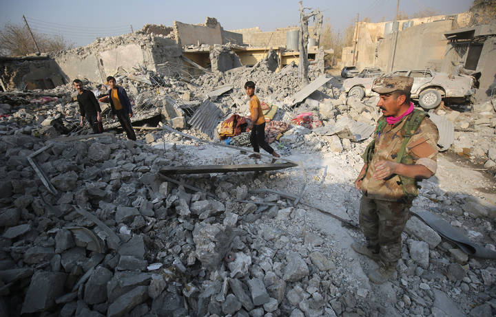 Hammam al_Alil residents inspect the damage caused by air strikes in their town, south of Mosul.