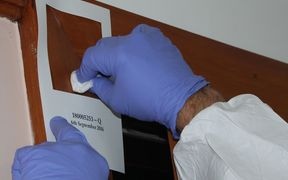 A close up photo of two hands with gloves on, swabbing within a 100 square centimetre stencil stuck to a wall. By swabbing within that area, testing companies get a sample that corresponds to Ministry of Health guidelines for meth.