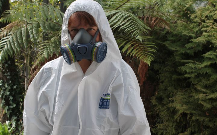 A photo of Katy Gosset wearing a mark and white protective suit and hood, ready to go into a meth house.