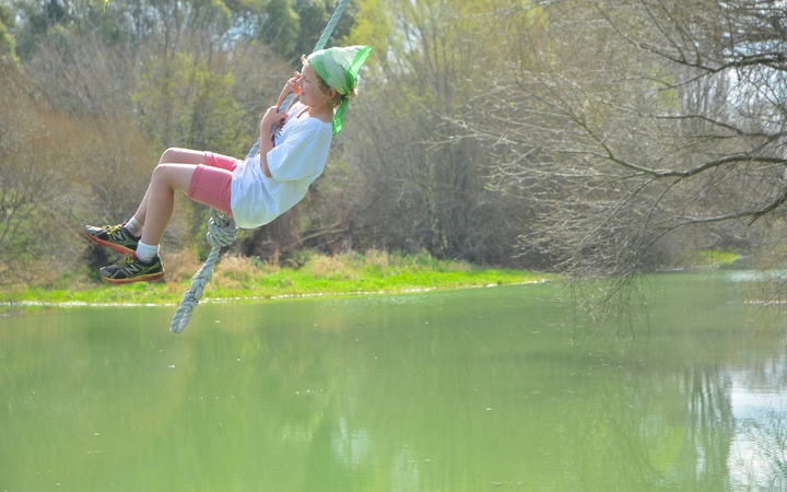 Rosie Glover swings over the Selwyn River. She does not swim anymore because of the toxic green slime covering large stretches of it.