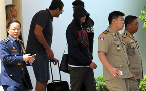 A refugee (3rd R) held under Australian custody in the Central Pacific island of Nauru is escorted by Cambodian police following his arrival at the Phnom Penh International airport on June 4, 2015.